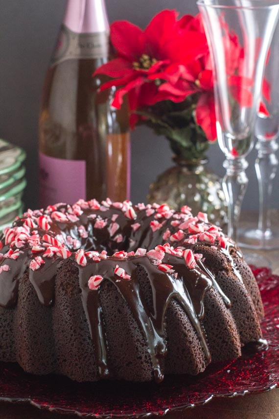 vertical image of low FODMAP Chocolate Peppermint Cake on a red plate with champagne and glasses in background