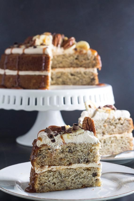 vertical image with Low FODMAP Salted Caramel Banana Cake in background and slice on white plate in foreground