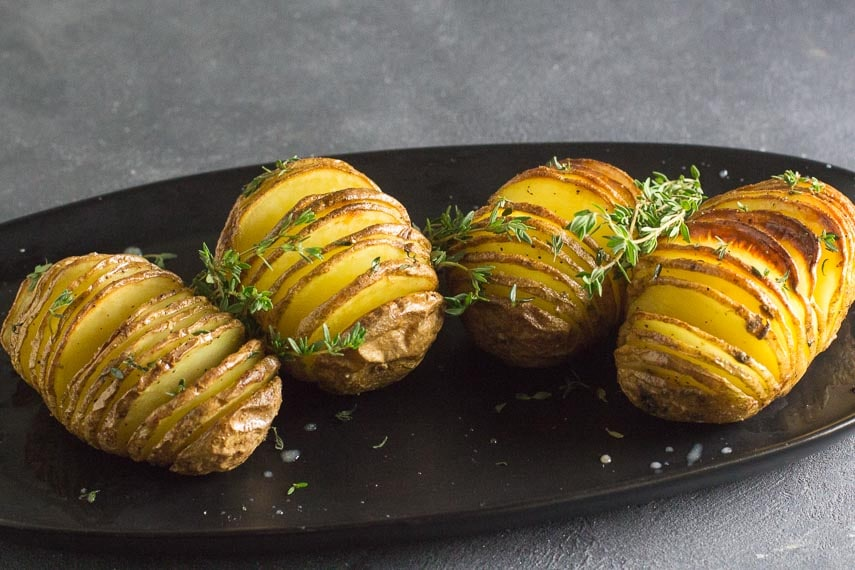 4 low FODMAP hasselback potatoes on black oval platter