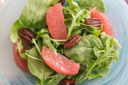 Greens with Grapefruit and Candied pecans on a blue glass plate
