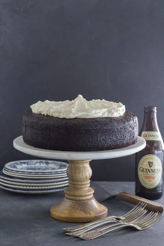 Low FODMAP Black Velvet Chocolate Guinness Cake on marble and wood pedestal; vertical image