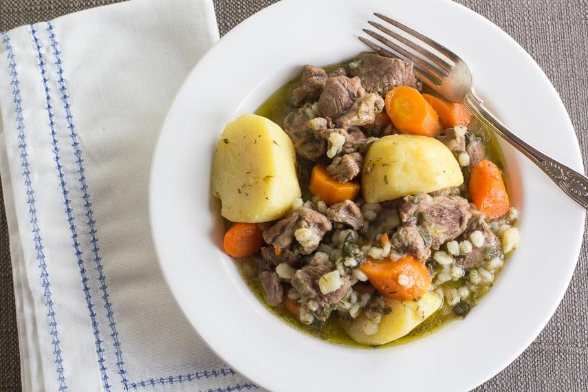Low FODMAP Irish Lamb Stew with barley in white bowl on taupe tablecloth