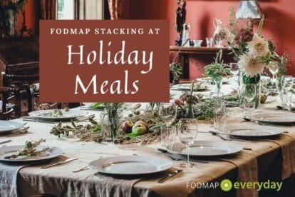 A dining table set for a holiday meal with white plates on a light brown table cloth, greenery and candle holders. With the text: FODMAP Stacking at Holiday Meals