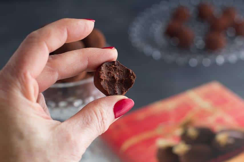 a bite out of a low FODMAP Dark Chocolate Truffle in manicured hand