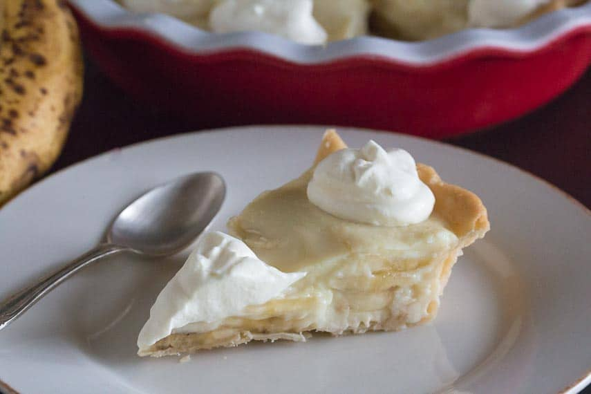 closeup of slice of low FODMAP banana cream pie on white plate