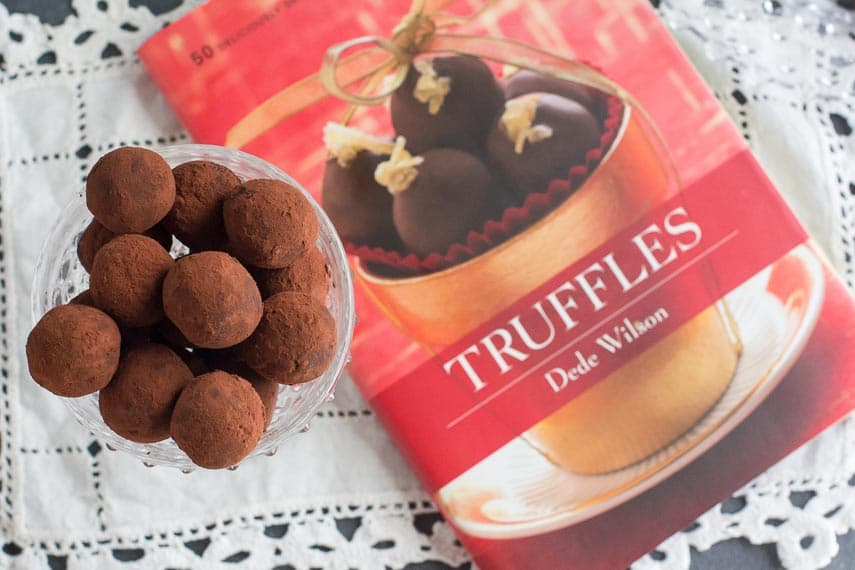 cocoa dusted low FODMAP dark chocolate truffles in bowl; overhead shot with TRUFFLES book in background