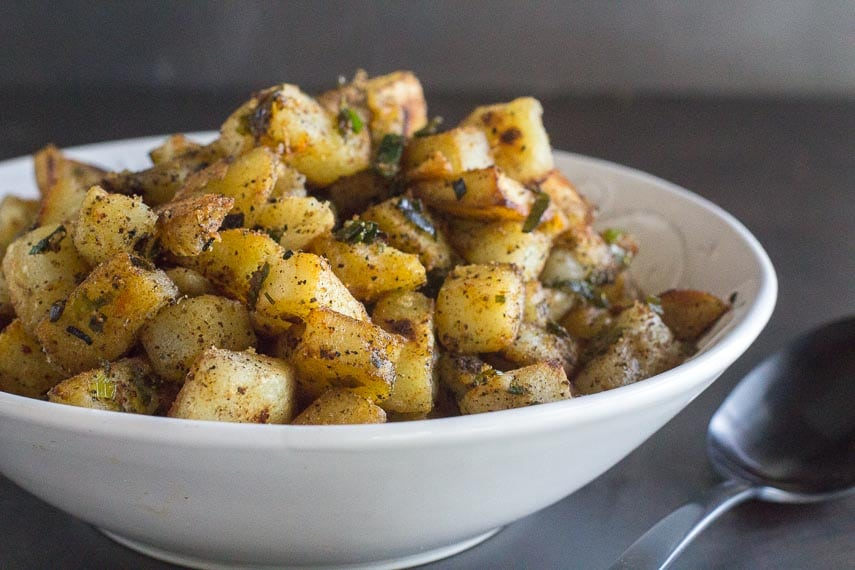 white bowl of low FODMAP home fries with serving spoon