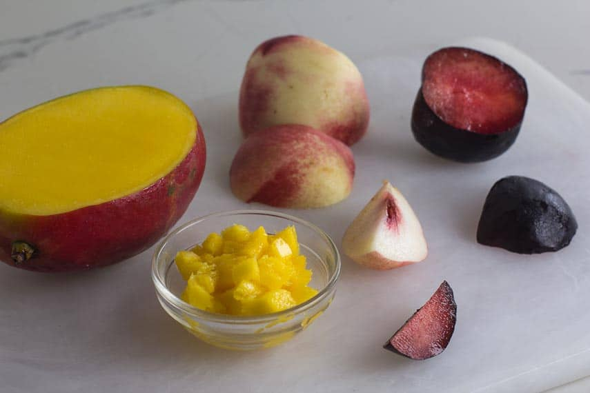 low FODMAP amounts of mango, white peaches and black plums on a cutting board