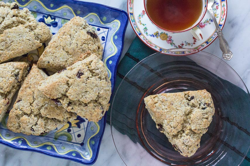 low FODMAP vegan scones piled on a platter and on a pink glass plate with a cup of tea