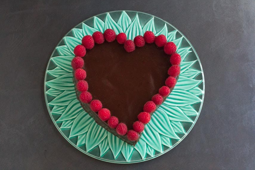 overhead shot of low FODMAP Raspberry Chocolate Truffle Cake on green platter