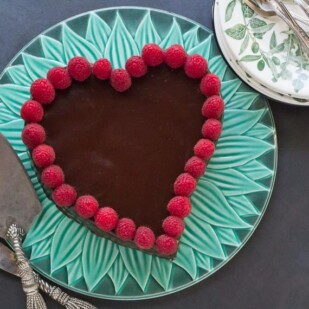 overhead view of low FODMAP Raspberry Chocolate Truffle Cake on green platter with plates