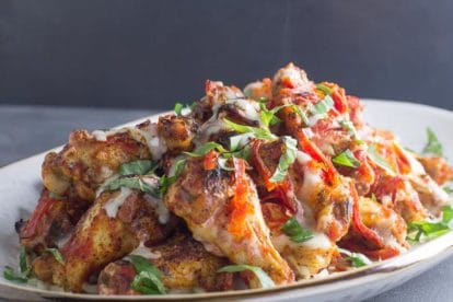 pile of low FODMAP pizza chicken wings on white plate with steam