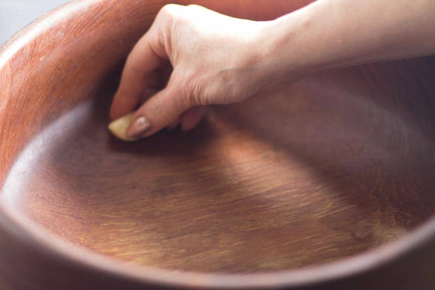 rubbing garlic in wooden bowl