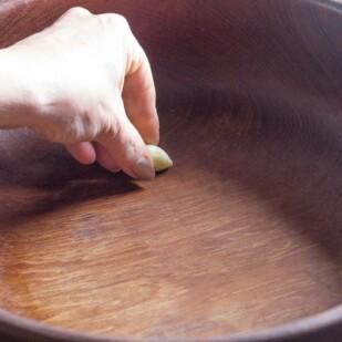 rubbing garlic on wooden salad bowl