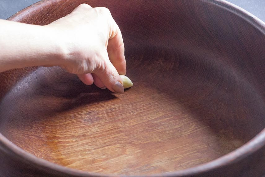 rubbing garlic on wooden salad bowl