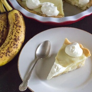 slice of low FODMAP banana cream pie on white plate with spoon