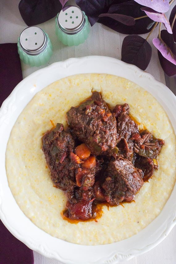 vertical image of low FODMAP short ribs with rosemary and orange on polenta in white bowl