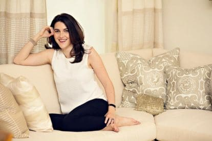 Danielle Capalino Sitting On A White Couch