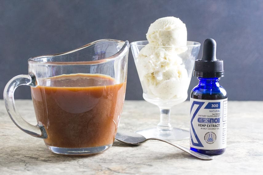 Elixinol CBD oil with lactose-free vanilla ice cream in background; salted caramel sauce in pitcher