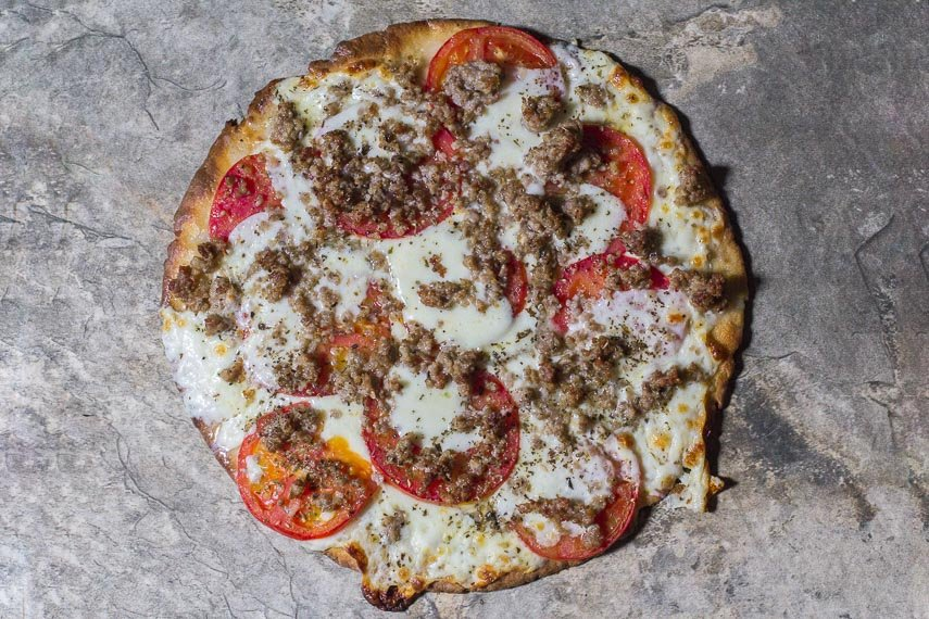 Low FODMAP CBD Oil Pizza with Sausage & Fresh Tomato on a stone surface