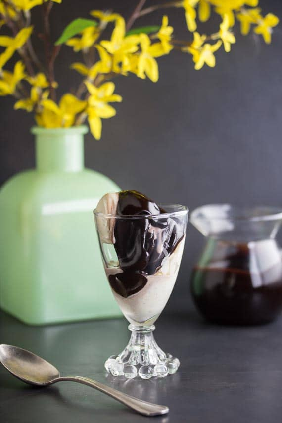 Low FODMAP CBD oil Hot Fudge Sauce on vanilla ice cream in glass dish against dark background