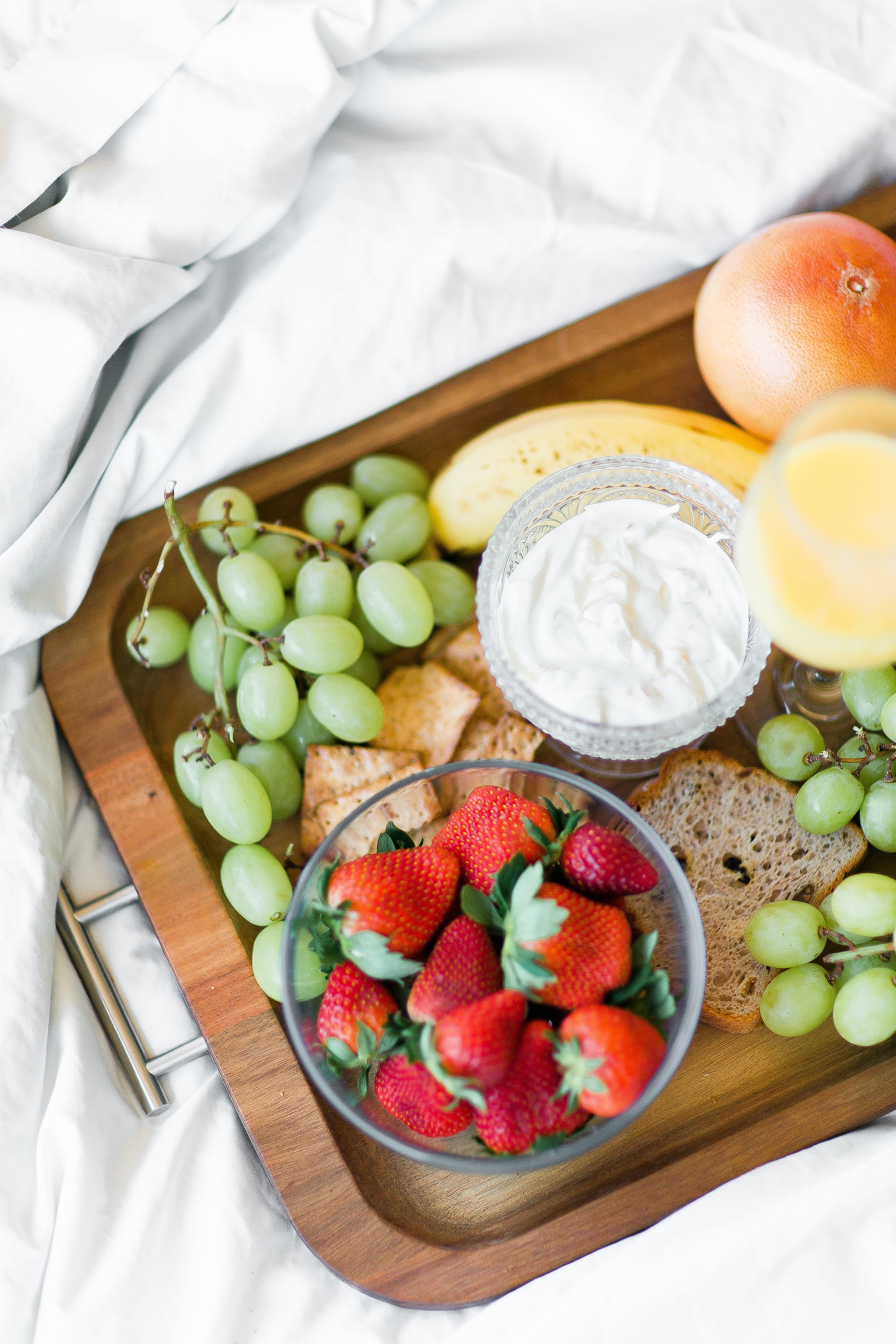 room service tray filled with fruit, crackers, bread and yogurt