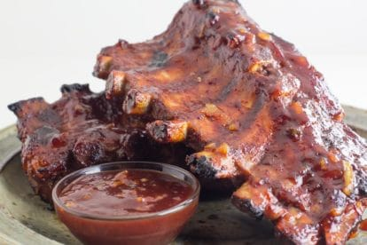 Low FODMAP Oven-Roasted Orange Marmalade BBQ Ribs on rustic plate with small glass dish of extra sauce