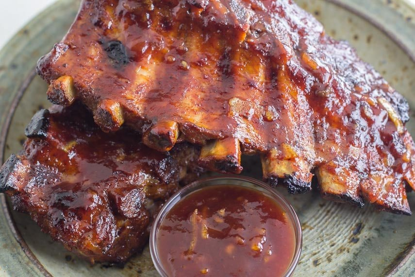 Oven-Roasted Orange Marmalade BBQ Ribs on rustic plate with small glass dish of extra sauce-5