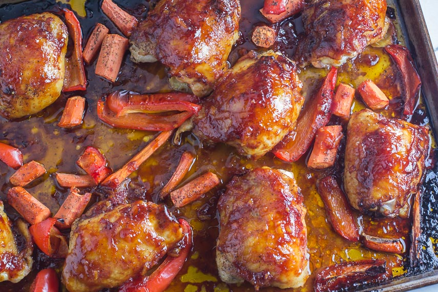 Low FODMAP Orange marmalade BBQ Sauce brushed on chicken, carrots and red bell peppers in a roasting pan