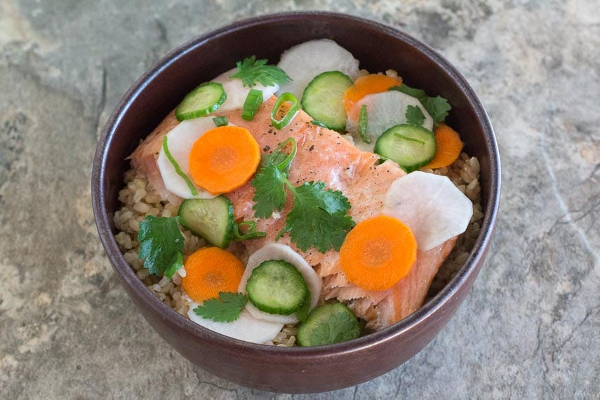 Low FODMAP Salmon Brown Rice Nourish Bowl with Quick Pickles in a brown bowl on a stone surface