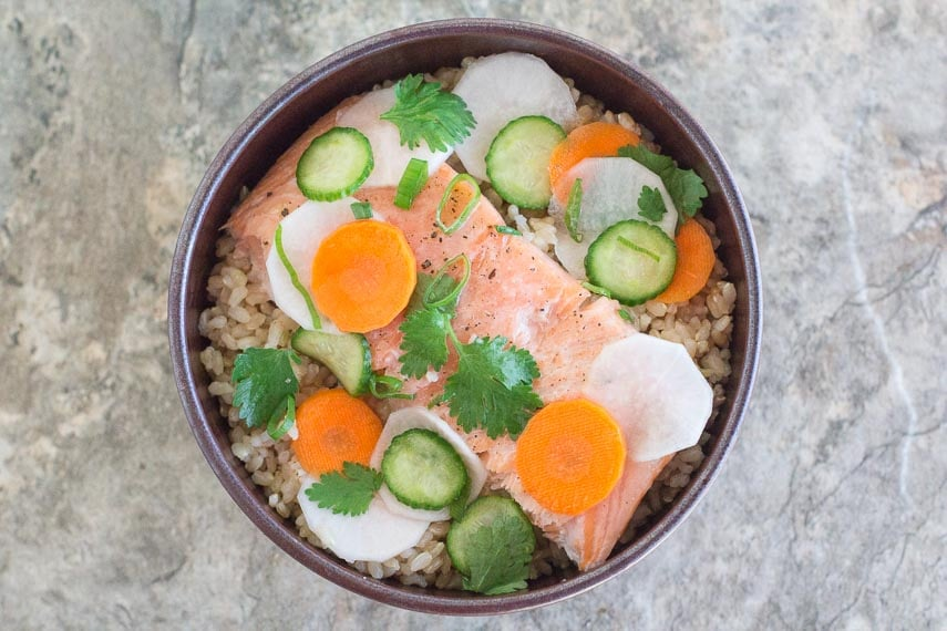 Low FODMAP Salmon Brown Rice Nourish Bowl with Quick Pickles on a stone surface
