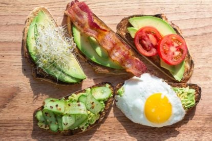 assorted low FODMAP avocado toast on a wooden board - great for breakfast, lunch or a snack