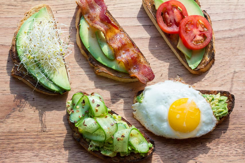 assorted low FODMAP avocado toast on a wooden board