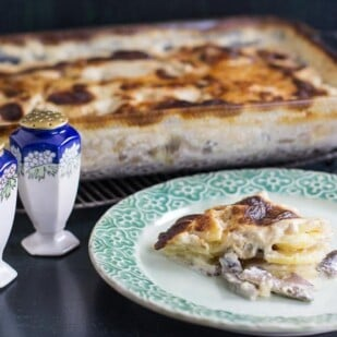 low FODMAP Potato Cheese Gratin with Mushrooms in casserole dish and on green plate