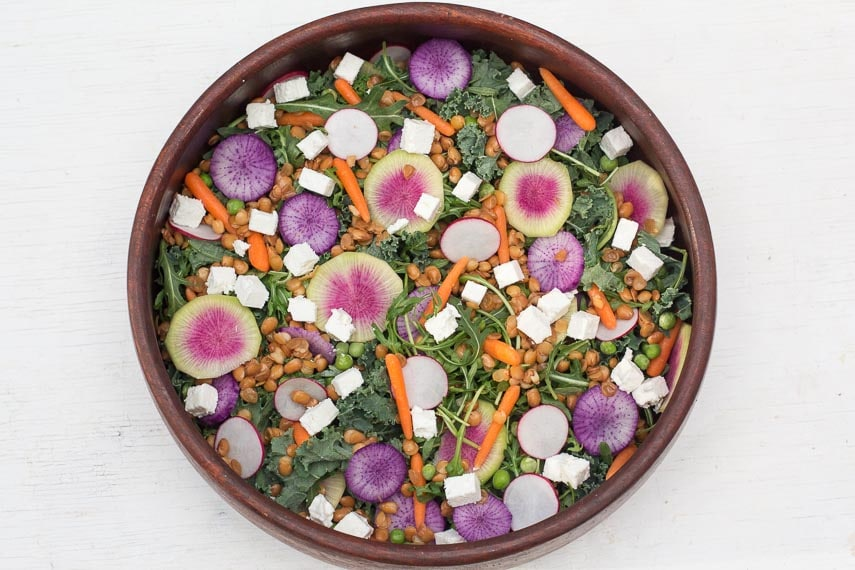 overhead image of low FODMAP Greens Salad with Radishes & Peas in wooden bowl