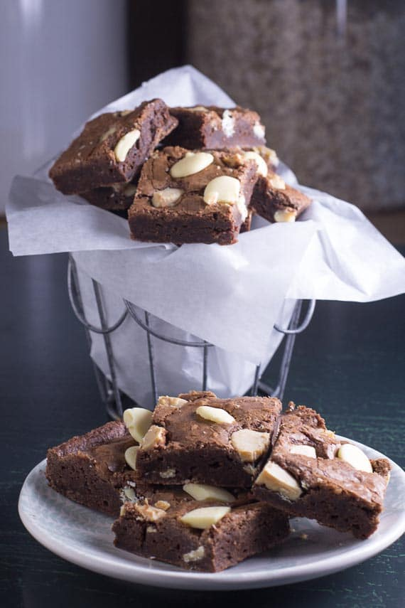 vertical image of low FODMAP Black & White Brownies on a plate in foreground and in a basket in background