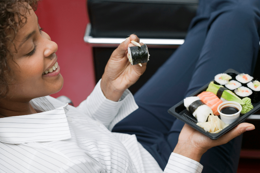 Woman enjoying a tray of sushi.