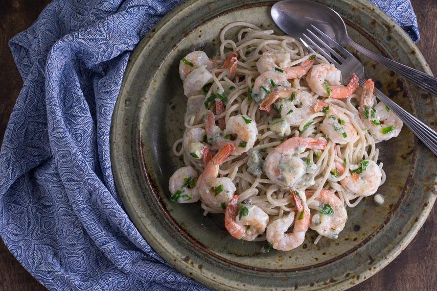 Low FODMAP Buffalo Shrimp Pasta on rustic ceramic plate