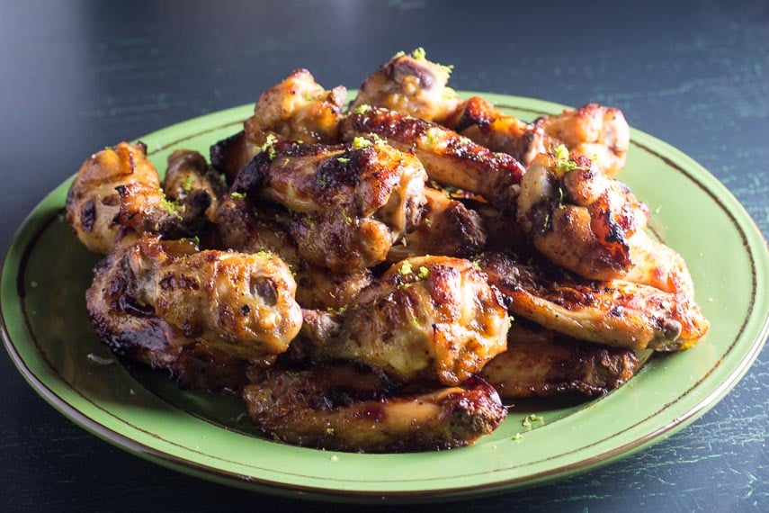 closeup of Low FODMAP Honey Roasted Chili Lime Chicken Wings on green plate