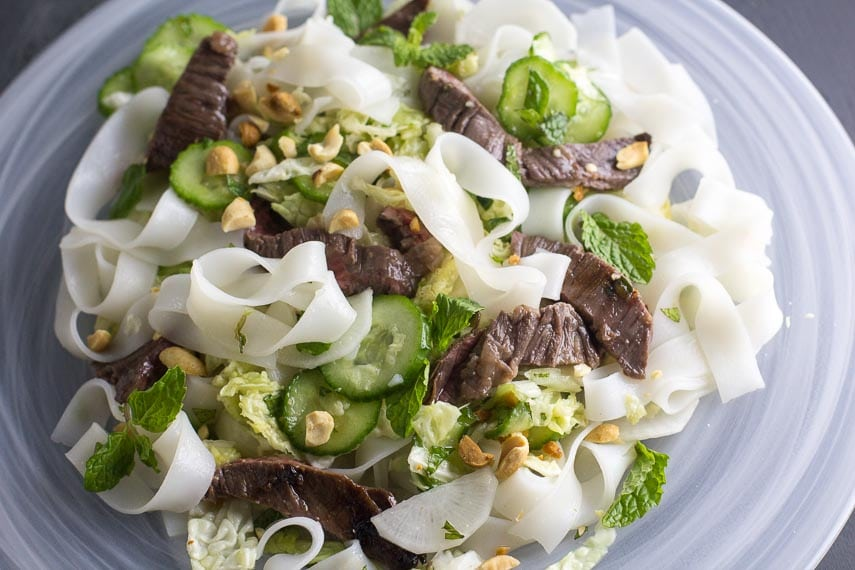 Low FODMAP Asian Steak & Noodle Salad with Mint & Peanuts on white plate