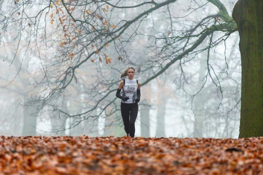 Female runner running on leaves in the woods.