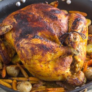 front view of low FODMAP whole roasted curry chicken with potatoes & carrots