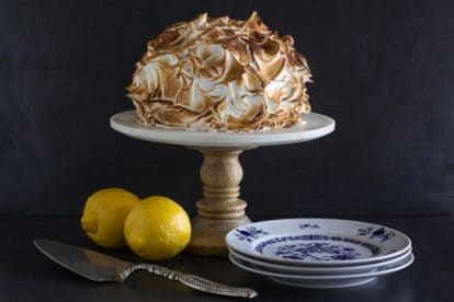 horizontal Low FODMAP lemon meringue cake on white pedestal with dark background