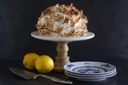 horizontal Low FODMAP lemon meringue cake on white pedestal with dark background