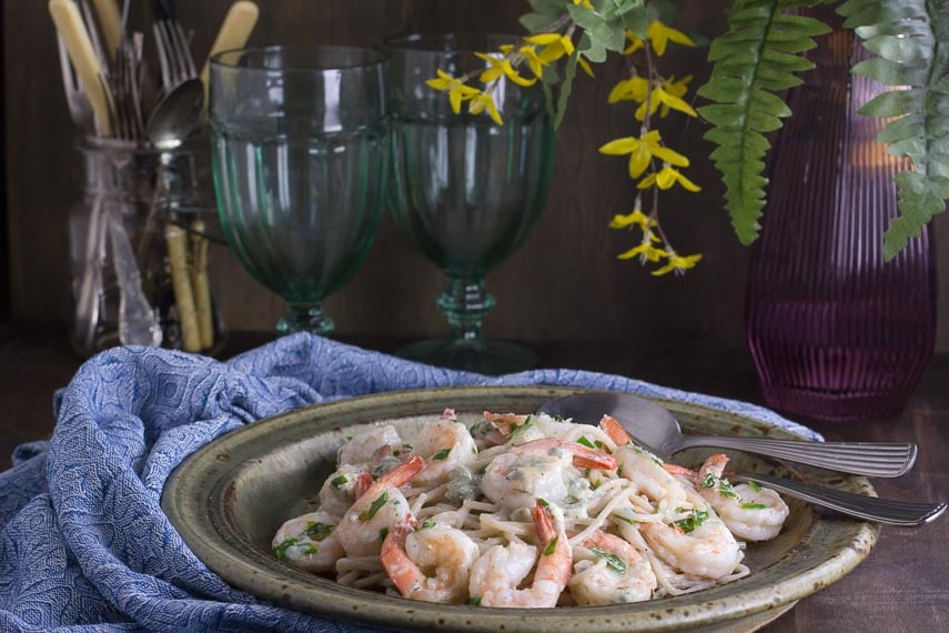 horizontal image of Low FODMAP Buffalo Shrimp Pasta on rustic ceramic plate