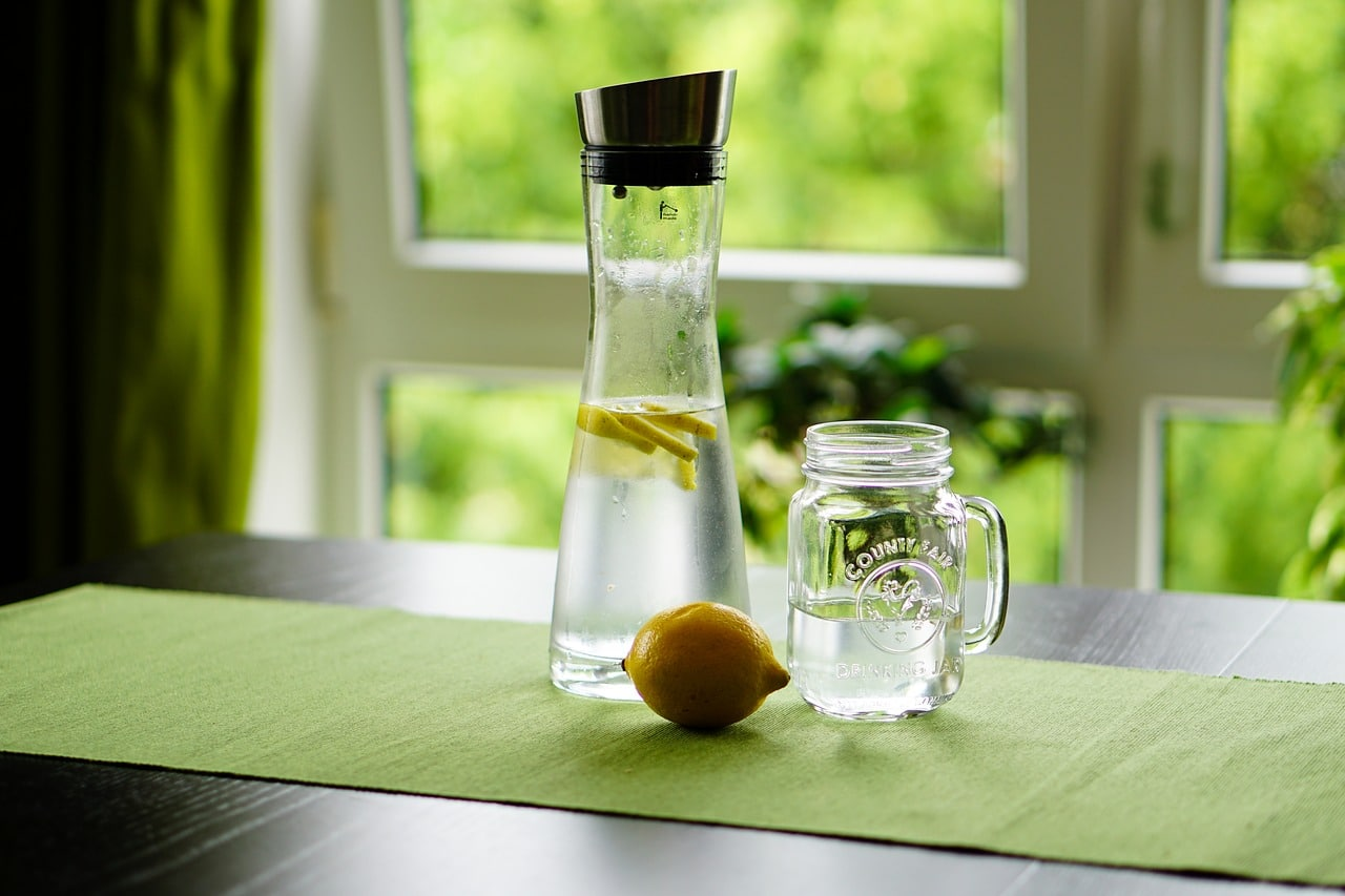 A carafe of fresh water and lemon set up by a window. Regular Girl can be added to water without any added flavoring or feel.