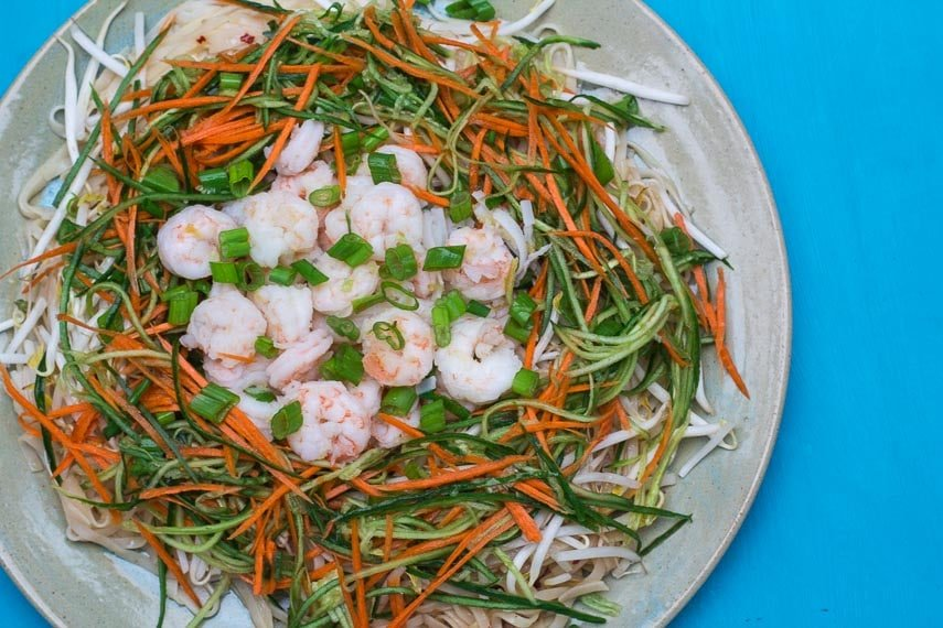 overhead image of Low FODMAP Spicy Sichuan Noodles and Shrimp Salad against turquoise background