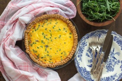 overhead image of ham & cheese low FODMAP quiche, whole, in pie pan with blue and white plates alongside