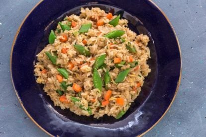 overhead image of low FODMAP fried rice with sugar snap peas and carrots on a blue plate