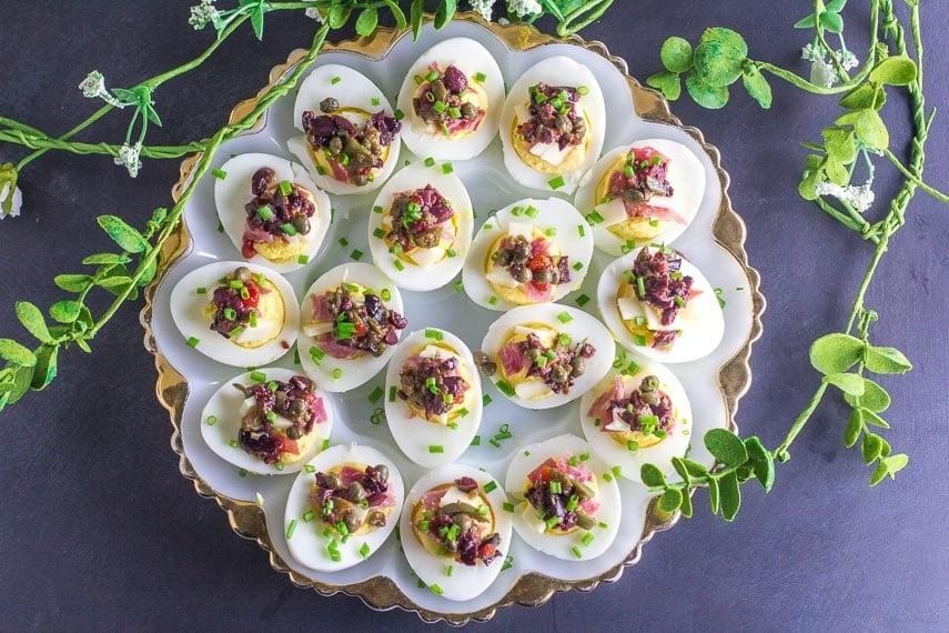 overhead of Low FODMAP Muffuletta Deviled Eggs on gold edged egg plate
